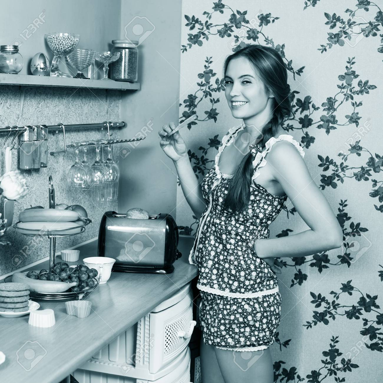 Attractive Housewife Eating Toast In Her Kitchen Stock Photo ...