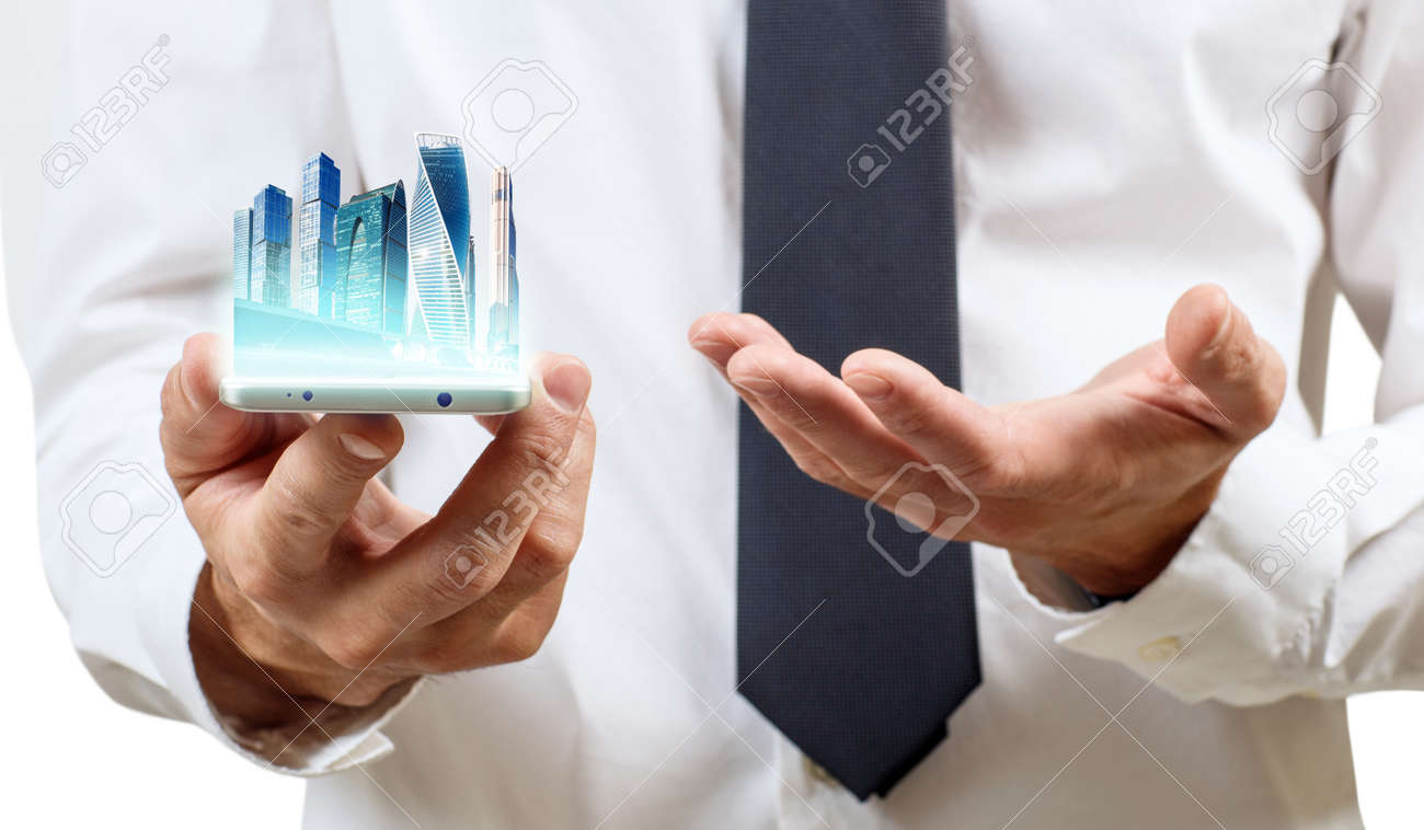 Business hand holds skyskrappers on outstretched hand. - 127830526
