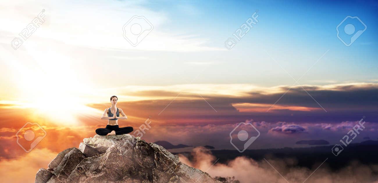 Young woman practice yoga on mountain peak cliff. - 131541753