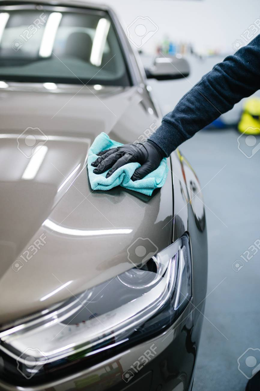 a man cleaning car with cloth, car detailing (or valeting) concept