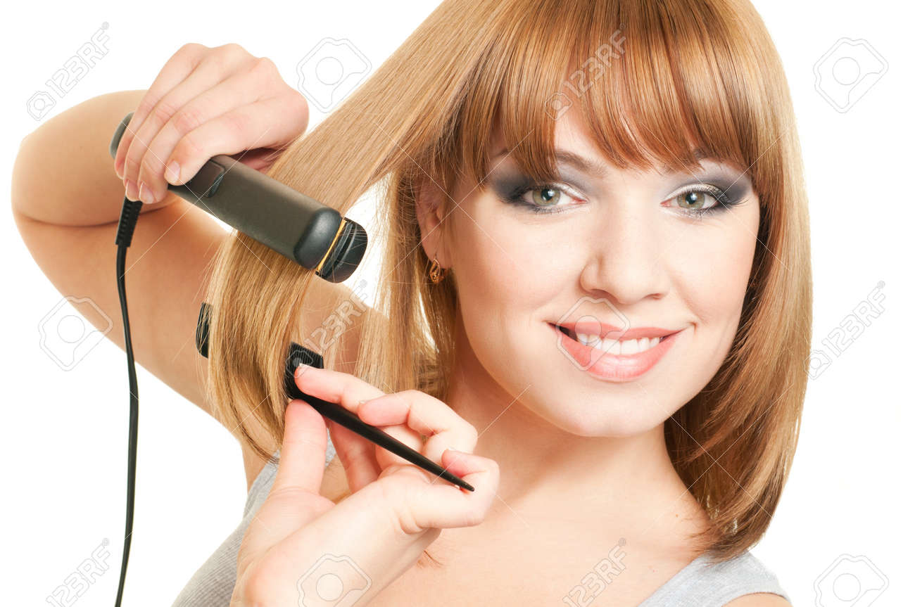 Portrait of beautiful young woman with fashion hairstyle holding crimper and comb Stock Photo - 9161500