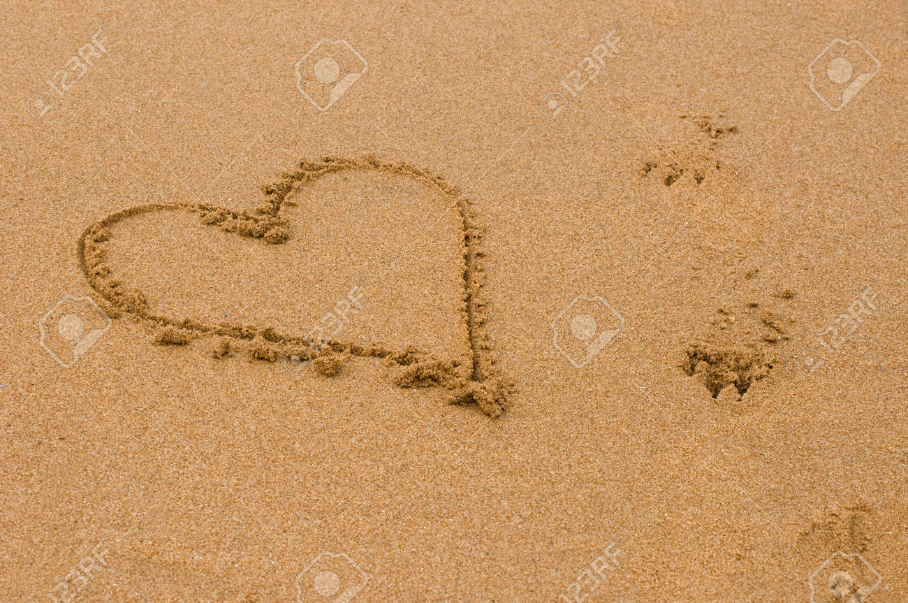 1ed4fc16f heart shape in the sand next to dog pawprints Stock Photo - 28463528