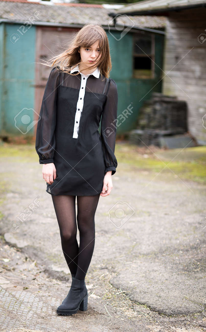 ... front of country house stables. Portrait of a beautiful young woman with  long hair wearing a black dress and boots standing d82ed36ae2f3