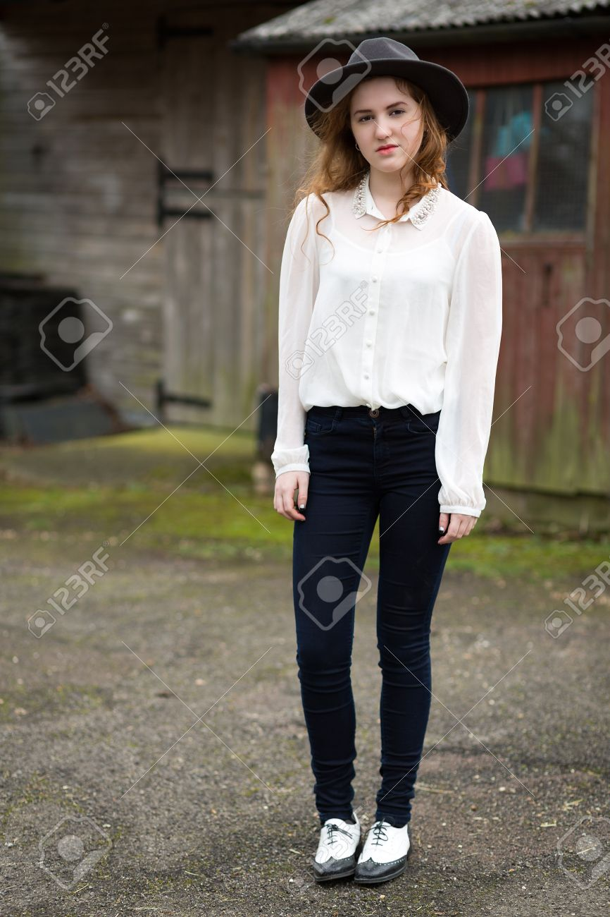 ... black shoes standing in front of horse stables. Portrait of a beautiful  ginger teenage girl wearing a hat 50d872a06269