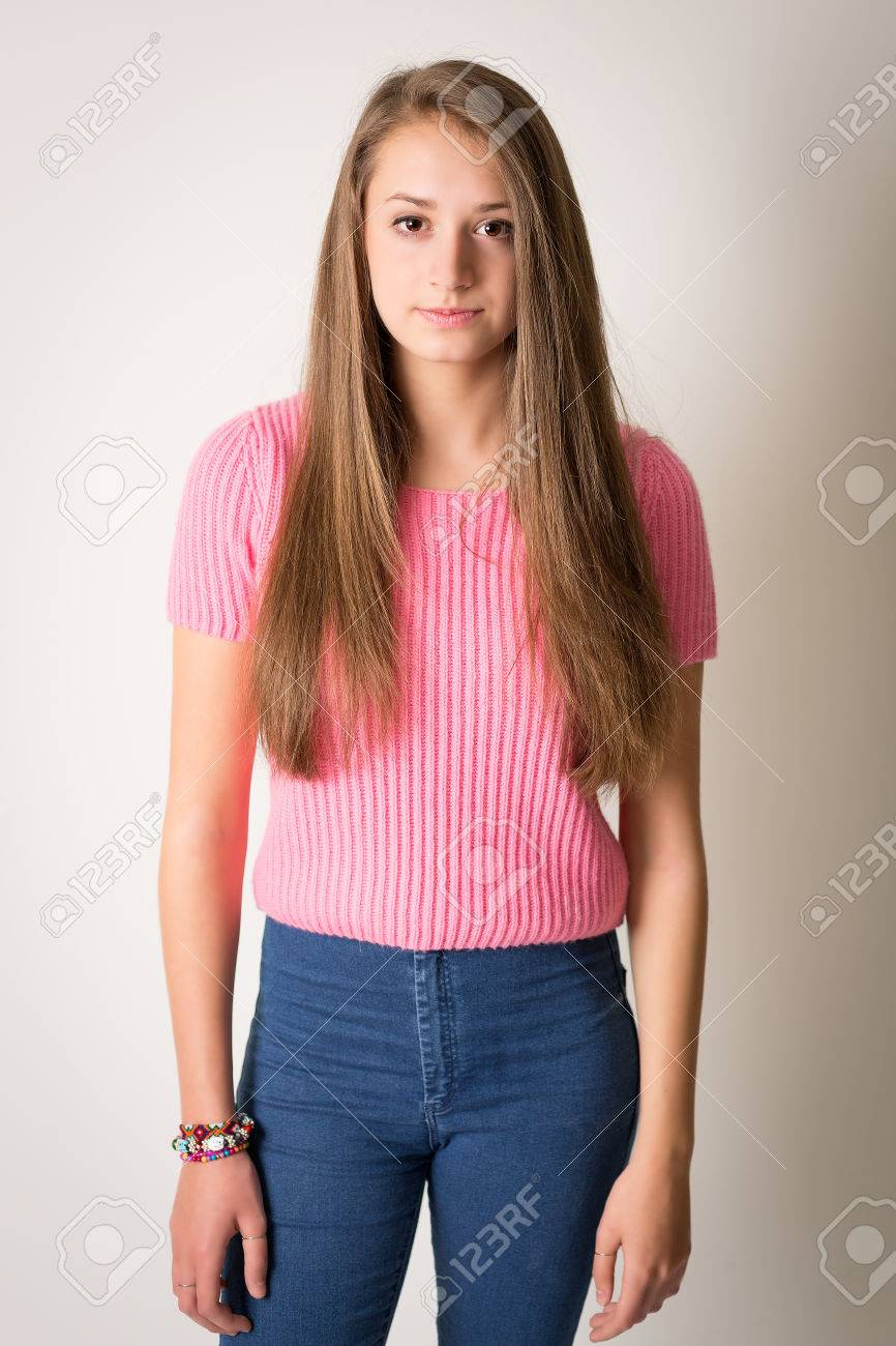 28550c045ddcf Portrait of a beautiful young woman with long brown hair in a pink woolen  top wearing