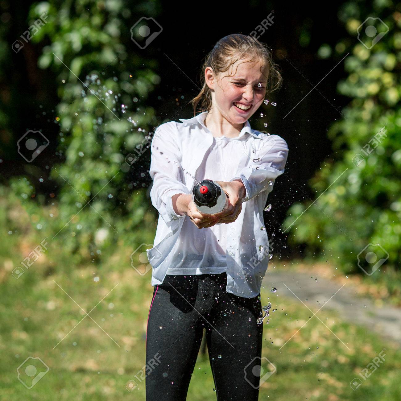 d821bc48cf48e Stock Photo - Wet teenage girl in white shirt and black legging squeezes  water from plastic bottle.