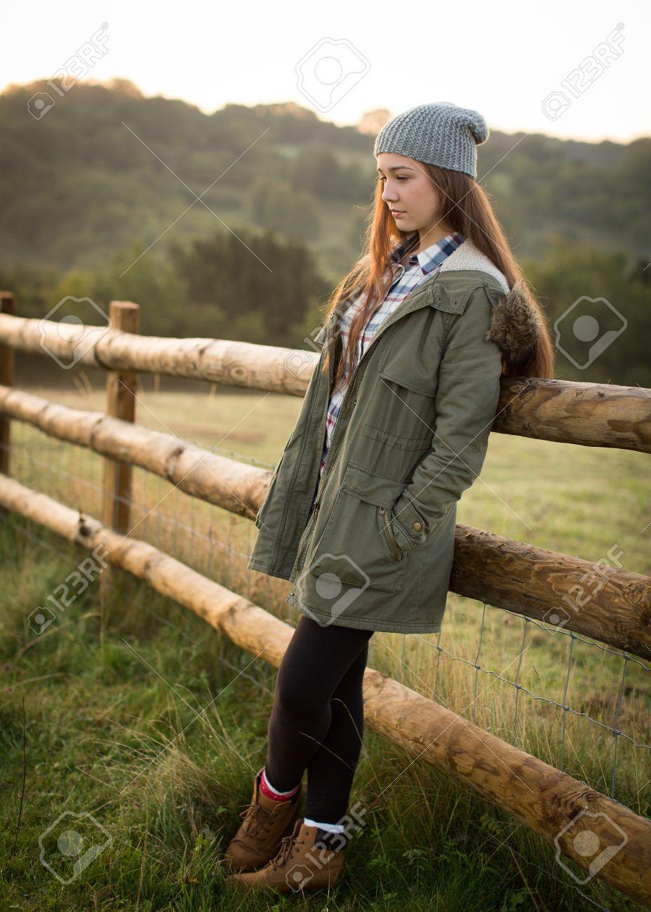Beautiful teen girl with long hair wearing a hat, long green..