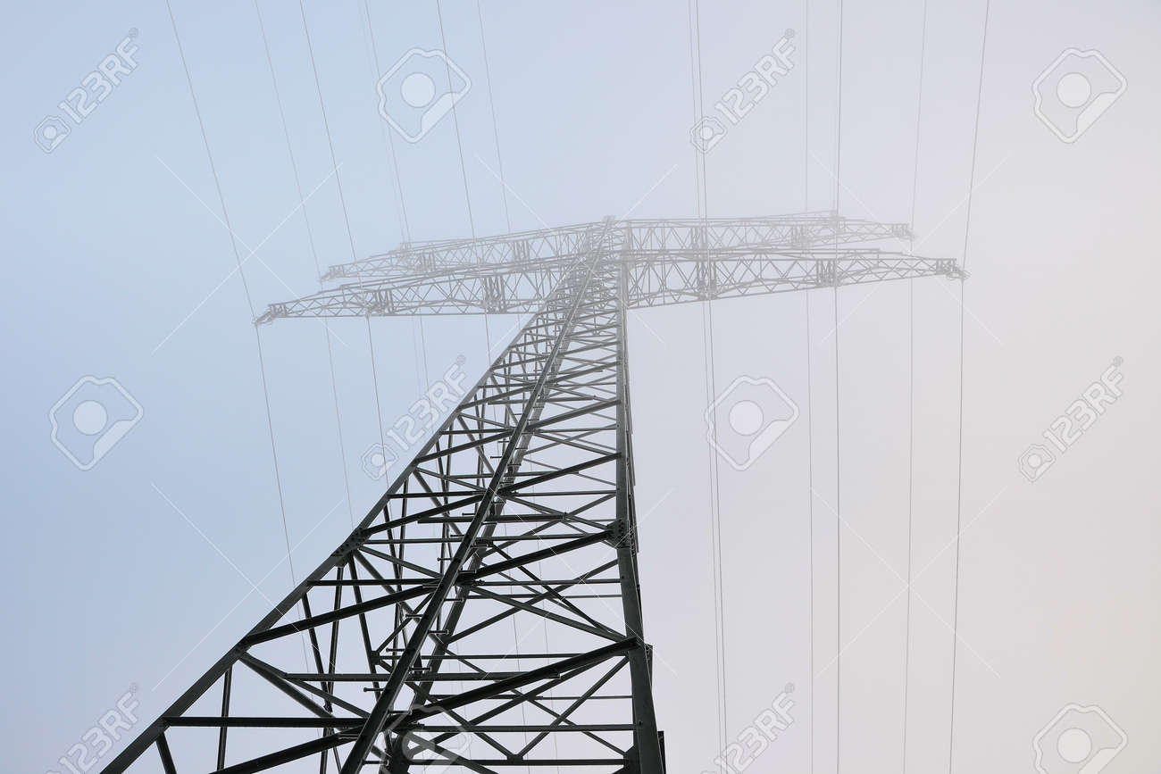 a power pole stands in a field in fog Stock Photo - 17365682