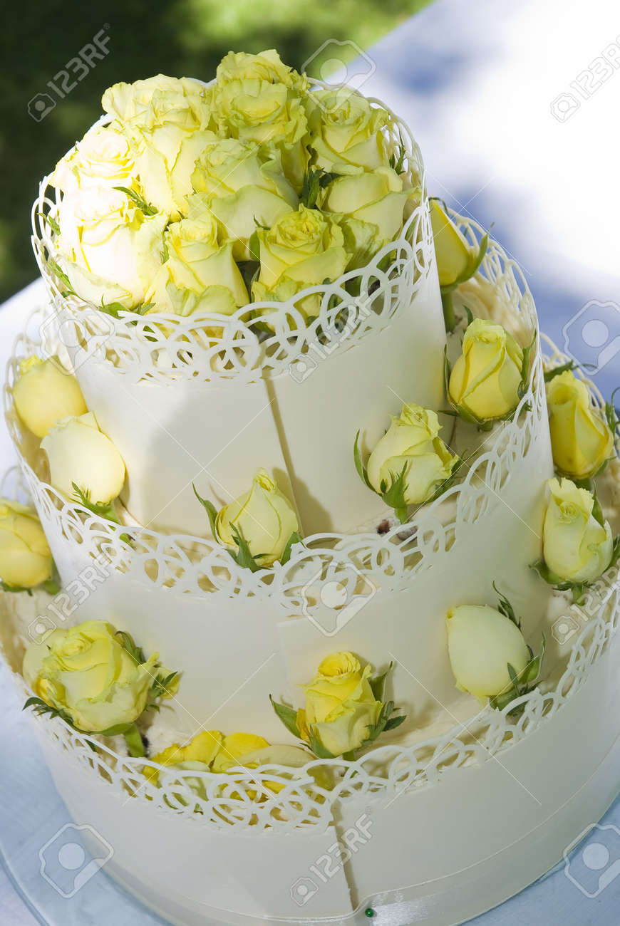 White Three-tiered Wedding Cake Decorated With Light Yellow Roses ...