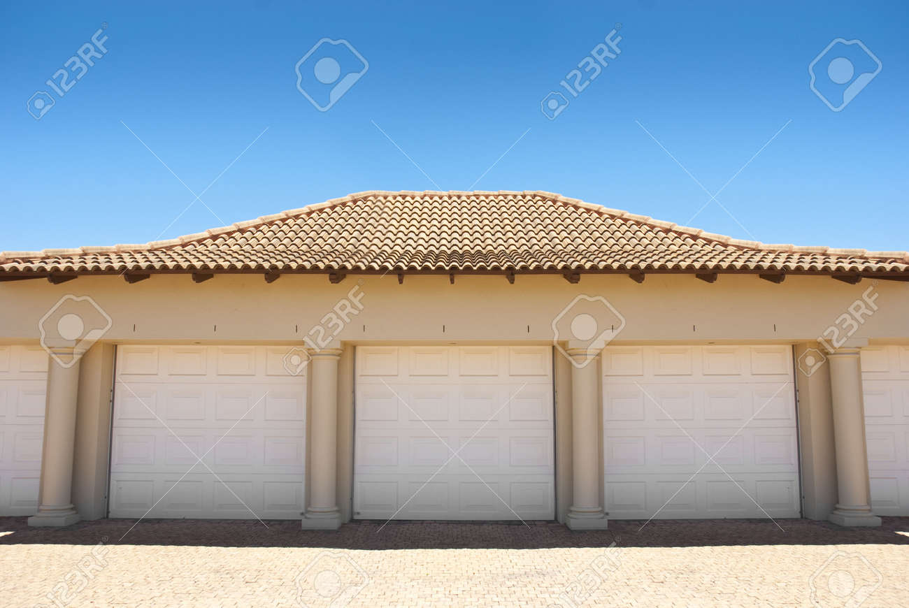White Triple Garage Doors With Blue Blue Skies Above And Driveway