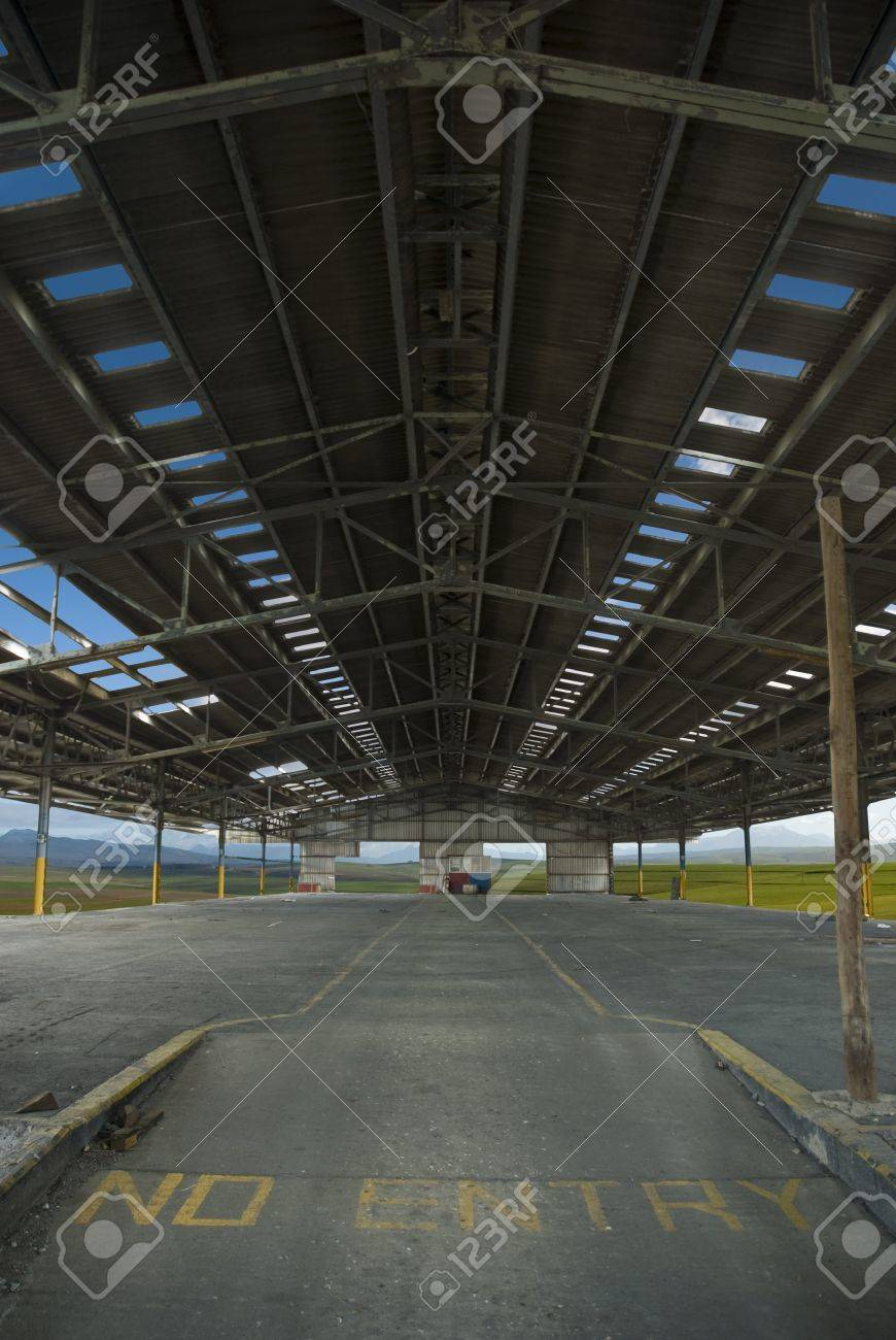 Huge old factory or industrial space with clouds and landscapes visible through all the openings Stock Photo - 10715595