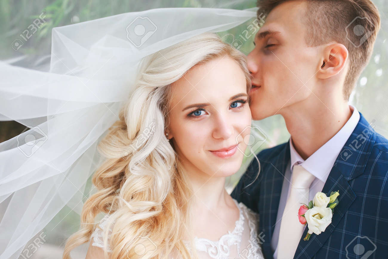 d767ab0c5b4 Stock Photo - Wedding couple kissing covered veil .Wedding romantic couple  is hugging each other. Beauty bride with groom
