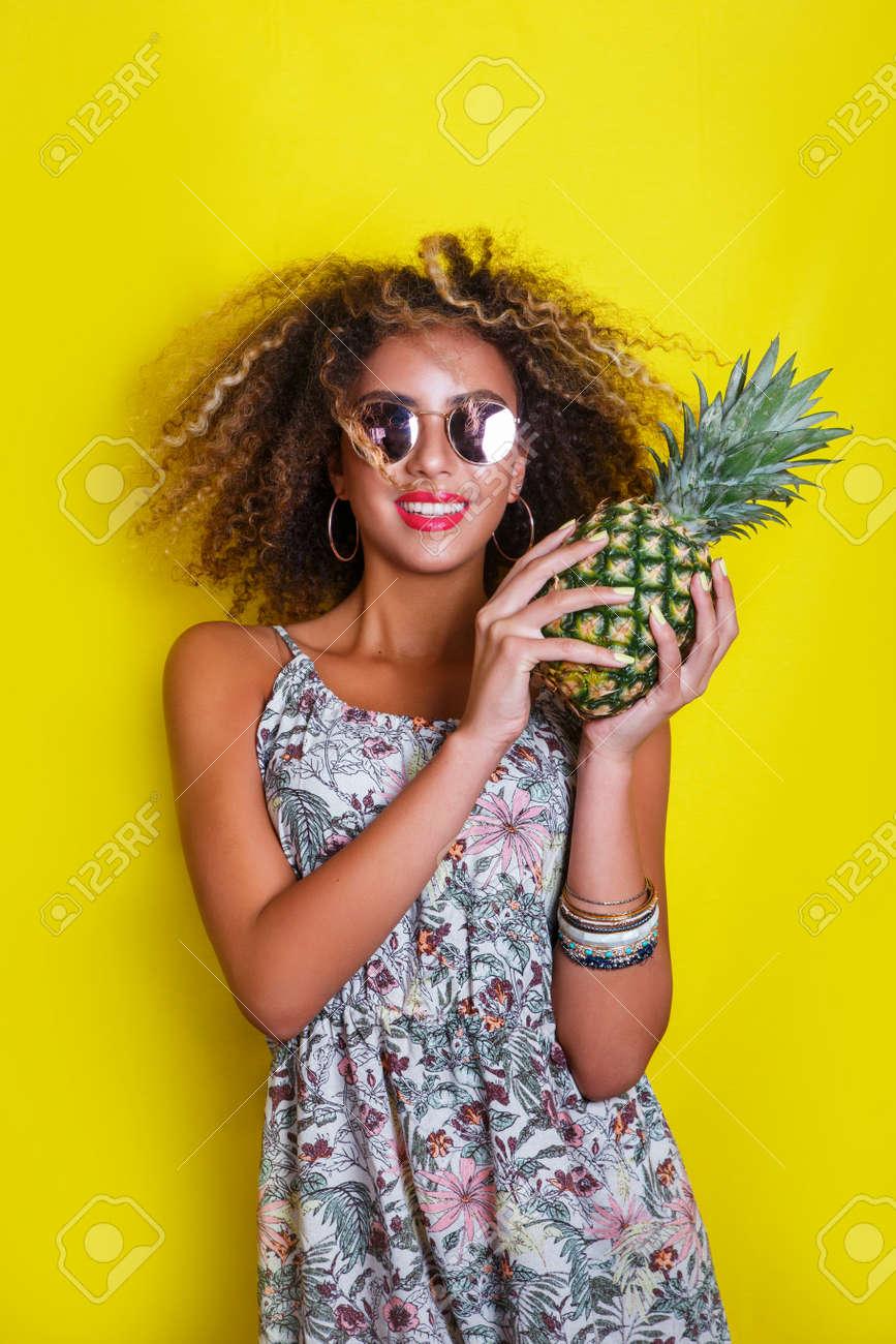 9d7fe30a41 Banque d'images - Fashion summer portrait afro fille américaine en lunettes  de soleil et ananas sur fond jaune