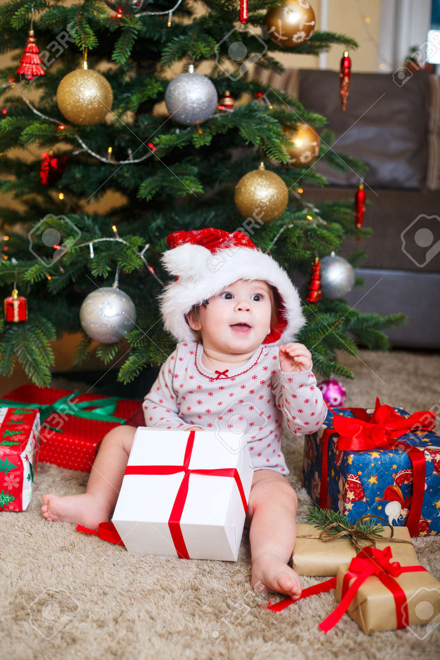 Cute Christmas Gifts For Girlfriend.Happy Cute Baby Girl In Santa Claus Hat Holding Christmas Gifts