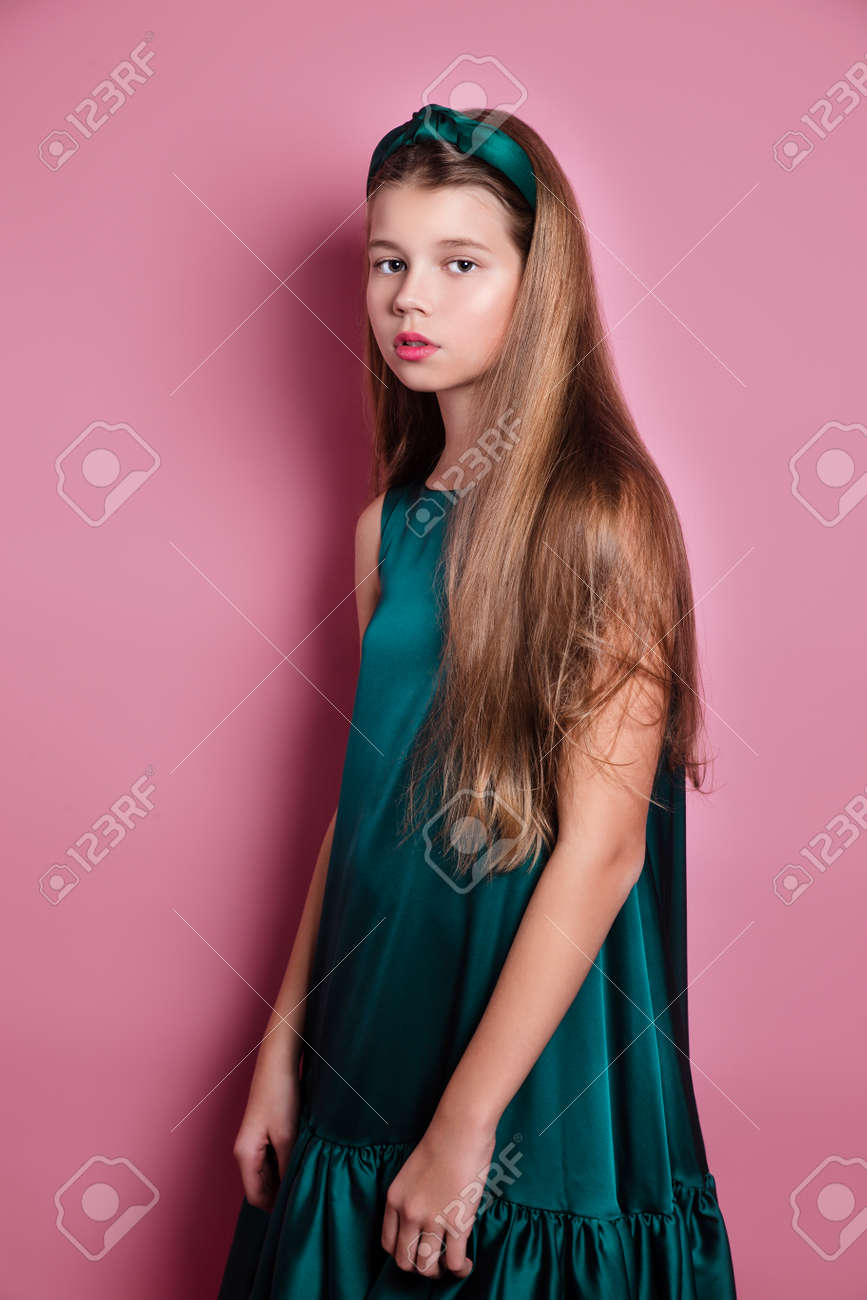Fashion portrait of beautiful young woman in a satin emerald dress on pink studio background - 146458927