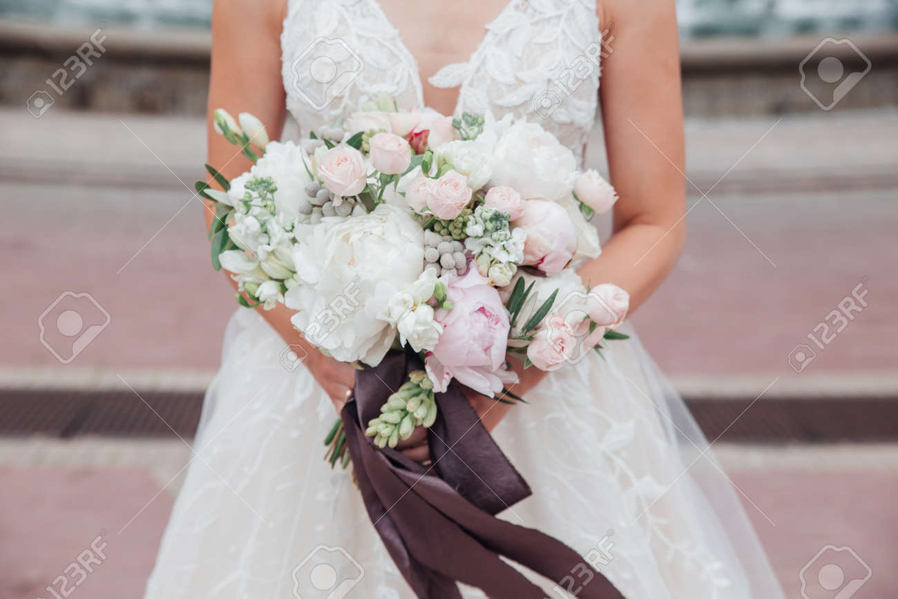 wedding bouquet in brides hands outdoor in wedding day - 142801188