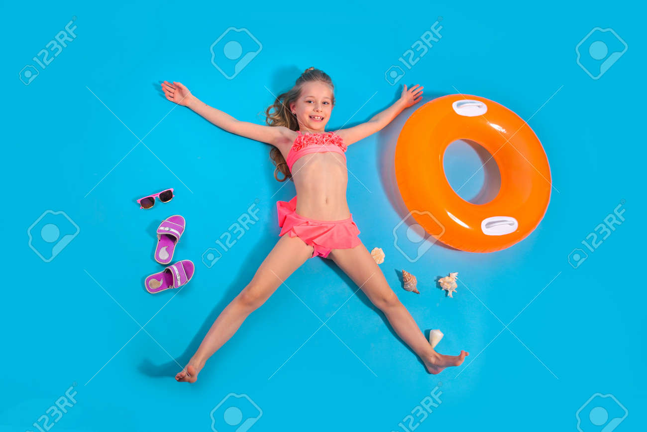 Pretty little girl relaxes with inflatable circle on blue background. Summer travel concept. - 146573389