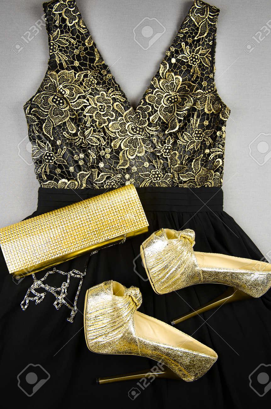 Zapatos De Tacón Dorado Bolso De Mano Y Vestido Negro Con Adornos Dorados Vista Superior