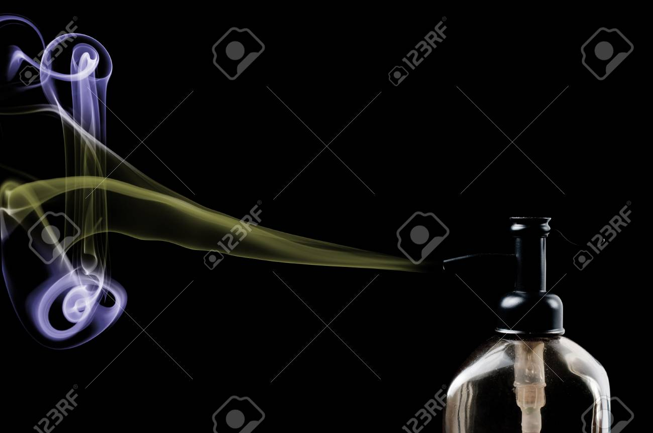 Dispenser bottle spewing out clored smoke on black background Stock Photo - 17200780