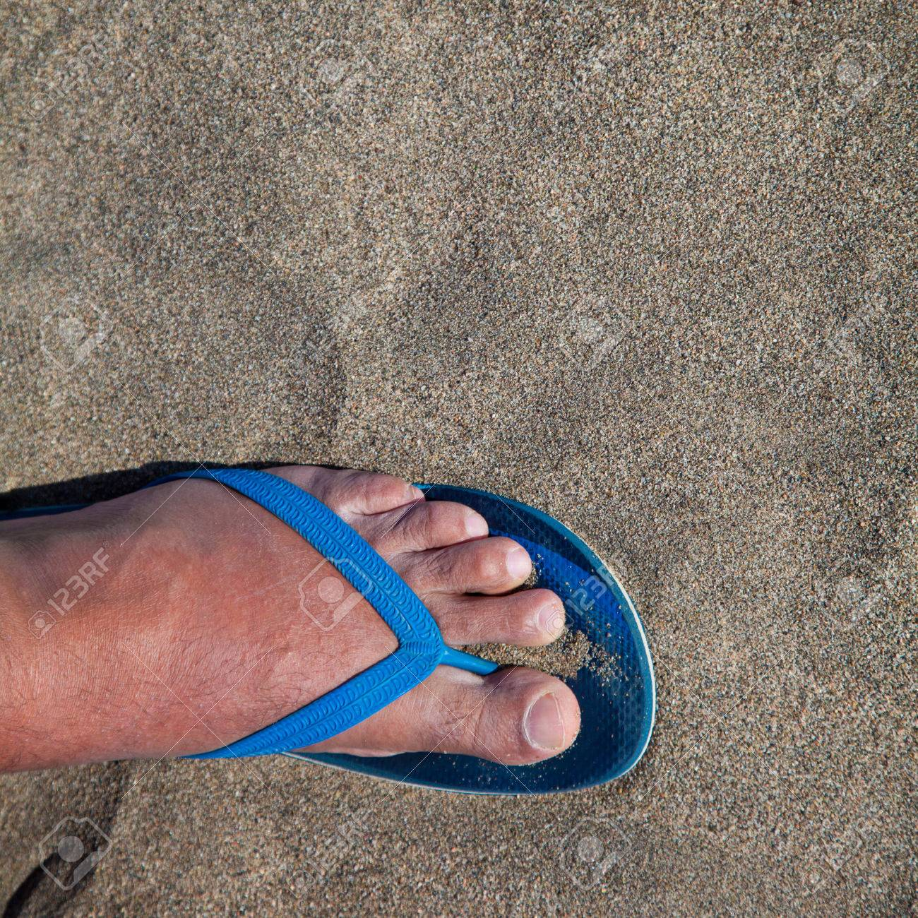 71b5aff5cf360 Feet of a man in thong sandals in beach sand Stock Photo - 59407338