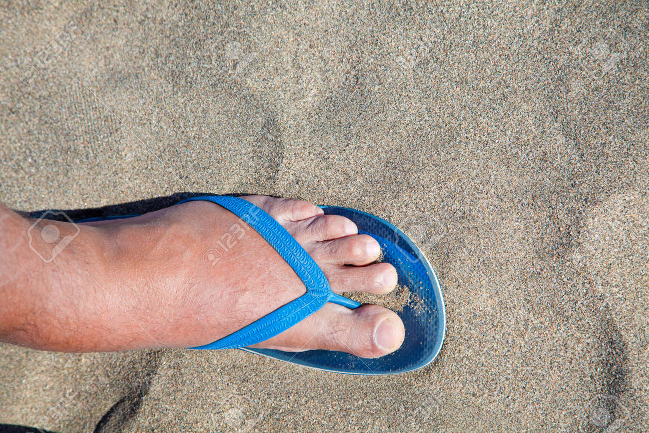 5e3397c106d0 Feet of a man in thong sandals in beach sand Stock Photo - 59407352