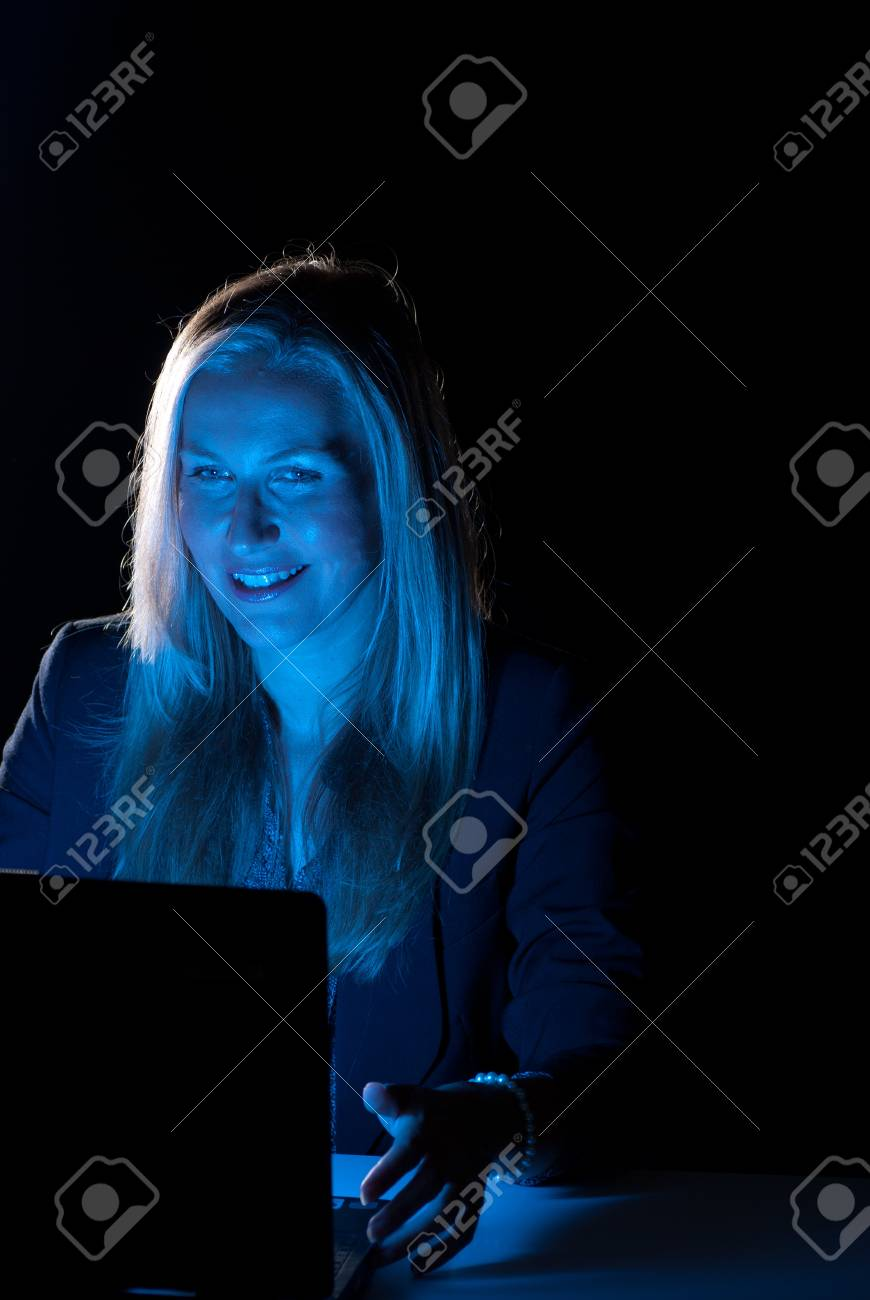 Businesswoman working late hours, with positive, smiling attitude Stock Photo - 7618883