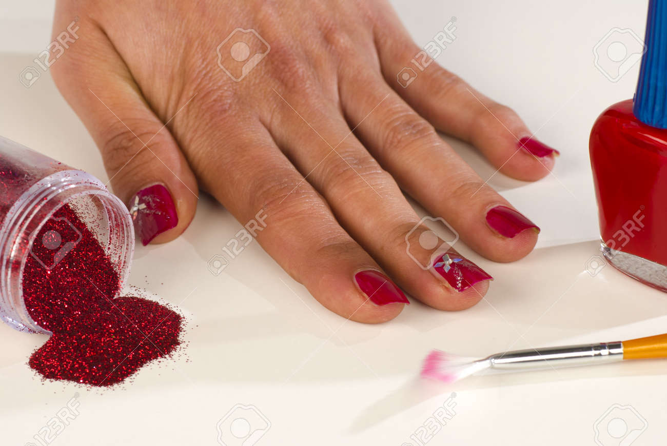 Hand With Finished Nail Decoration Surrounded By Nail Art Utensils ...