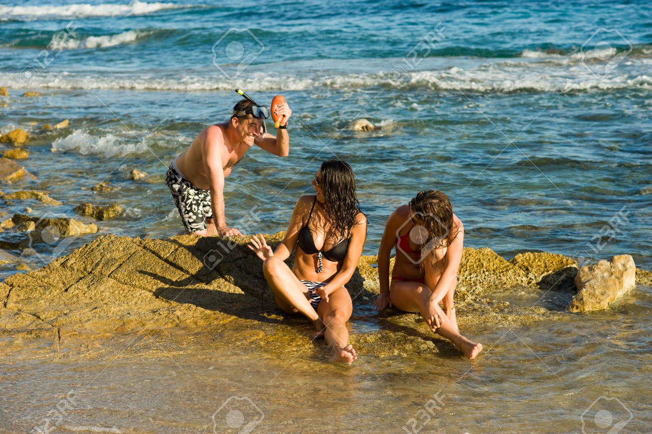 Typically persistent guy harassing sunbathing girls on the beach Stock Photo - 14942725