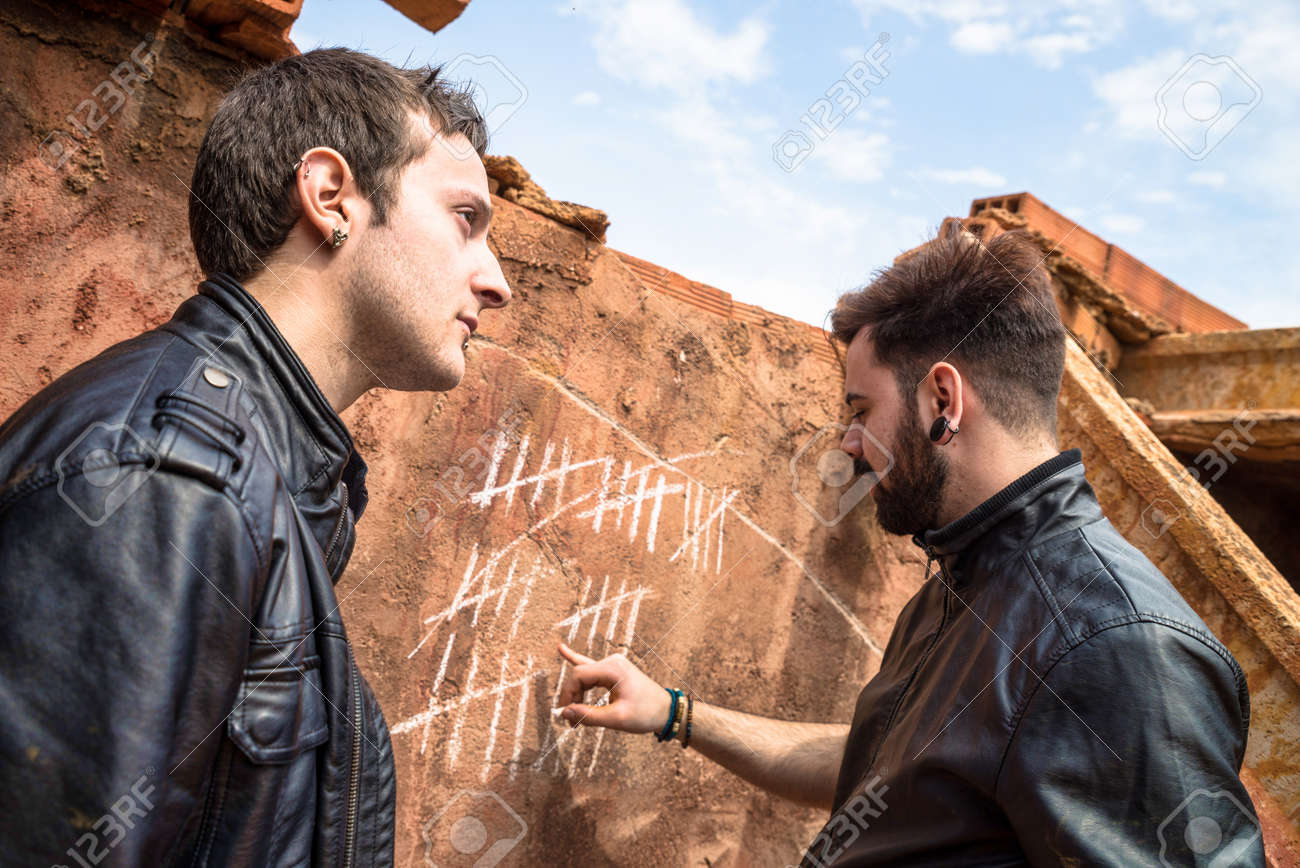 two guys couning days with chalk markings on a wall stock photo
