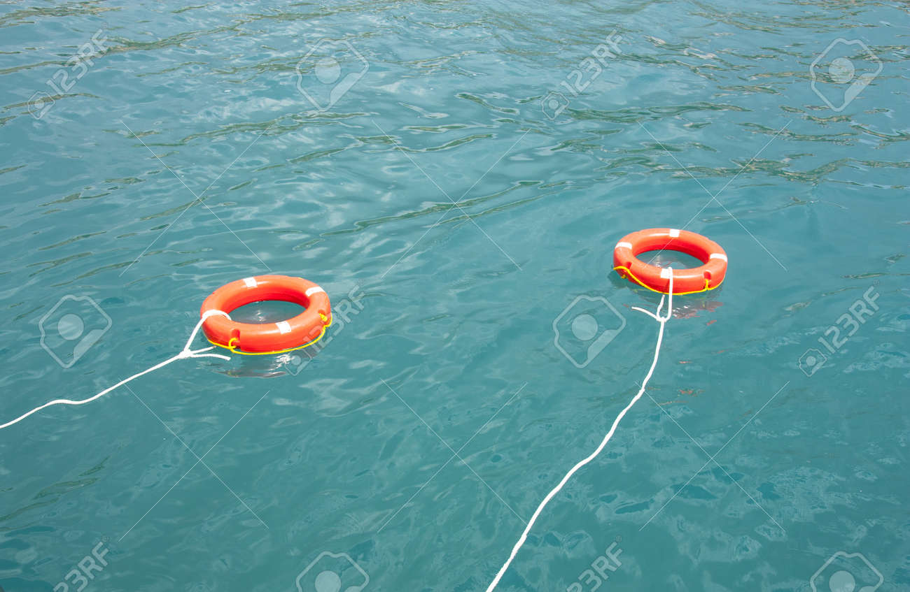 Safe water support aid circle with rope  Rescue red life buoy on wooden background of ship or boat  Helpful object Stock Photo - 21924412