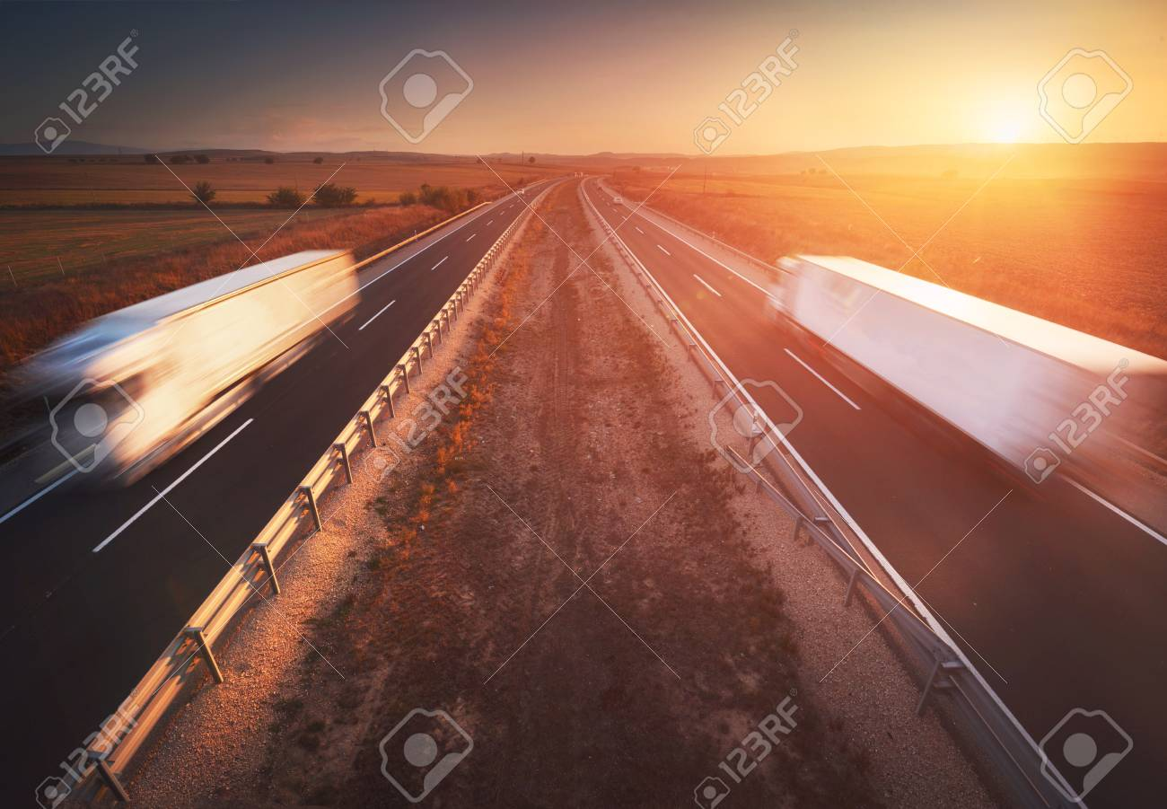 Trucks in the highway, dramatic sunset, motion blur. Cargo, transportation concept - 112674223