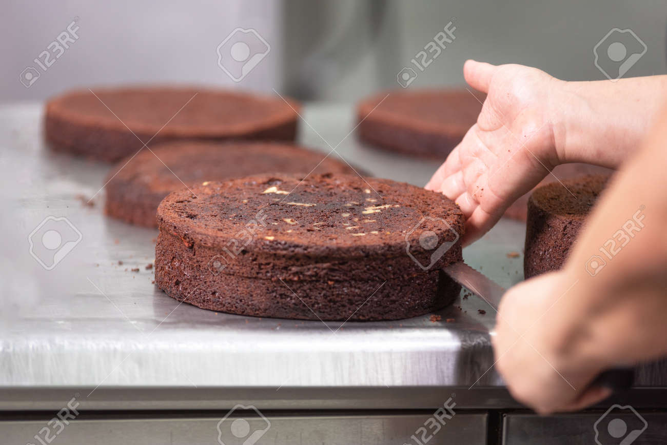 Professional confectioner making a delicious cake in the pastry shop. - 117557183