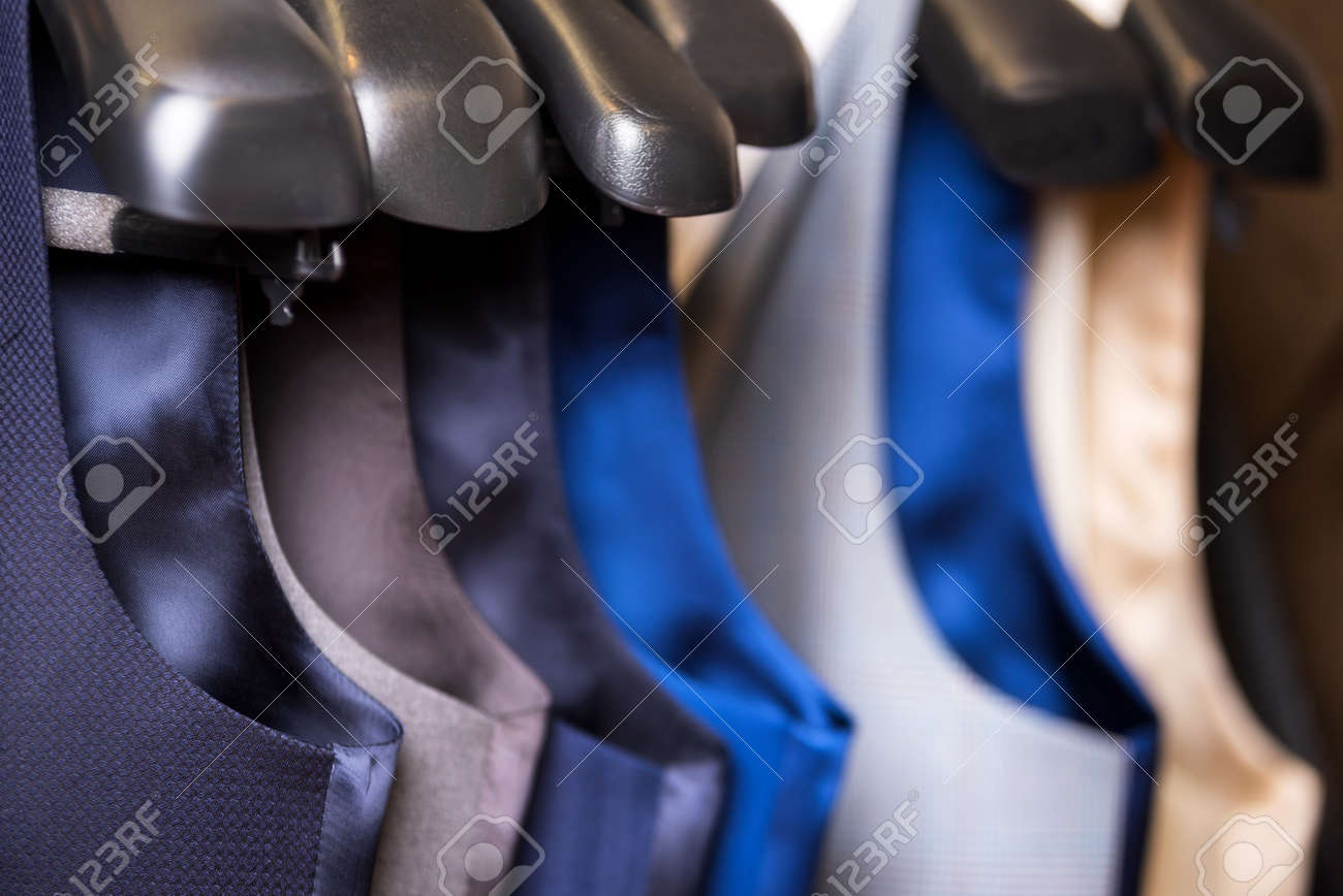 Stylish mens vest close up. Male svest hanging in a row. Mens Clothing, shopping in boutiques. vest and suits in a male luxury store. - 124787971