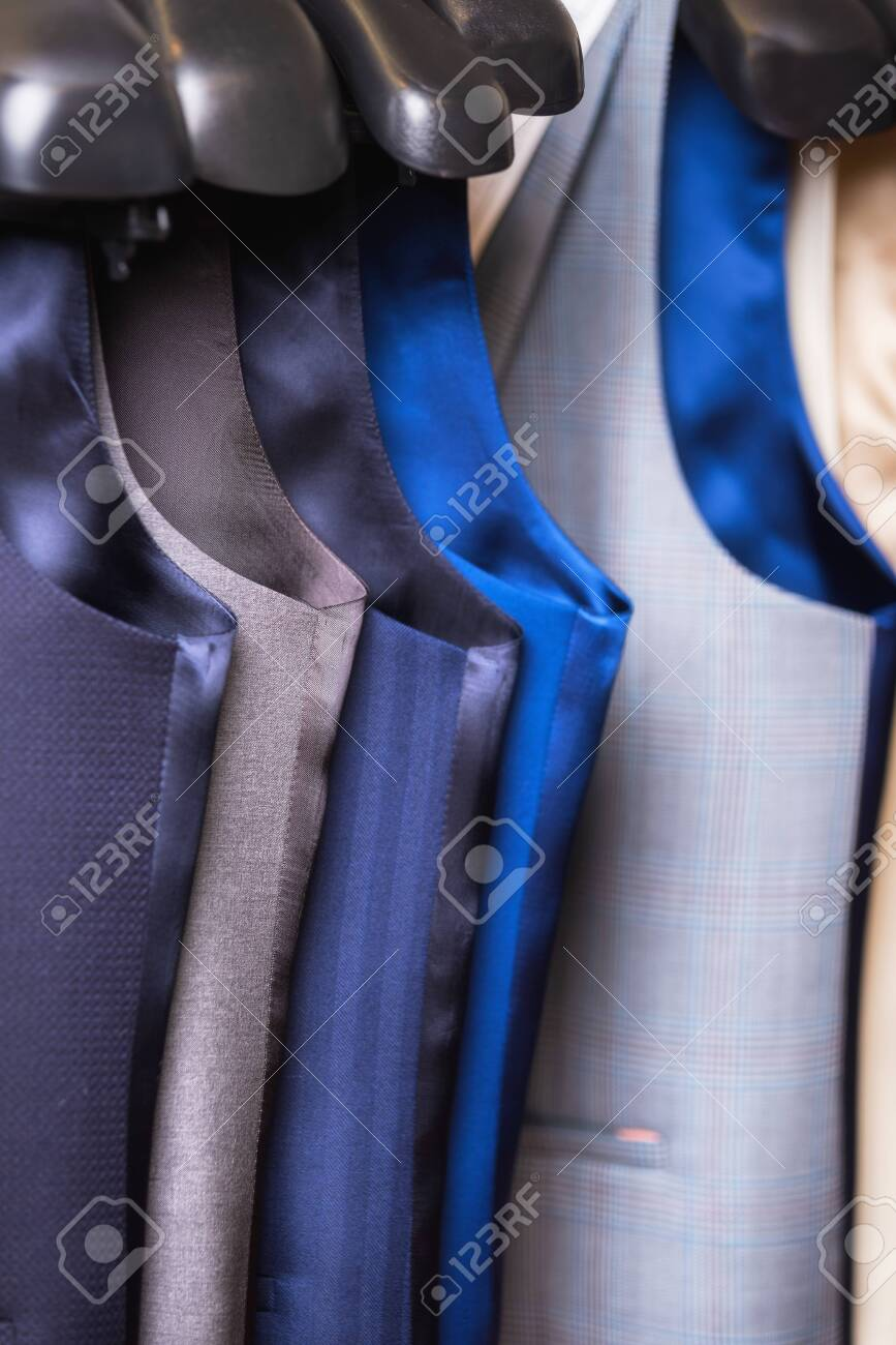 Stylish mens vest close up. Male svest hanging in a row. Mens Clothing, shopping in boutiques. vest and suits in a male luxury store. - 124787972