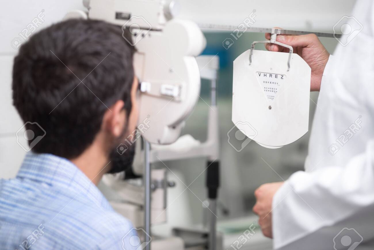 male doctor ophthalmologist is checking the eye vision of handsome young man in modern clinic. Doctor and patient in ophthalmology clinic. - 127134409