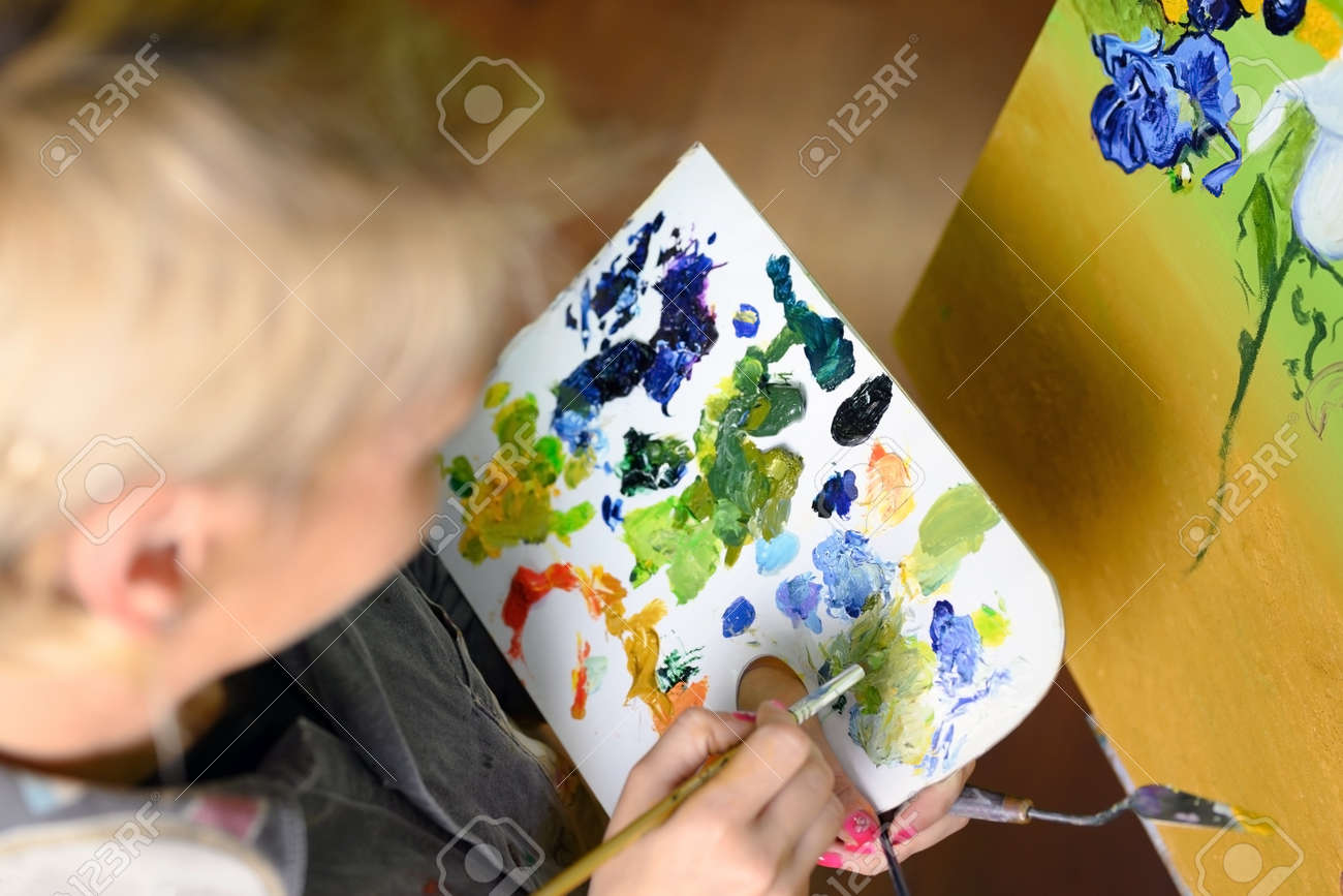 Female Artist mixes paints on the palette, painter at the studio, creator makes piece of art. - 169997528