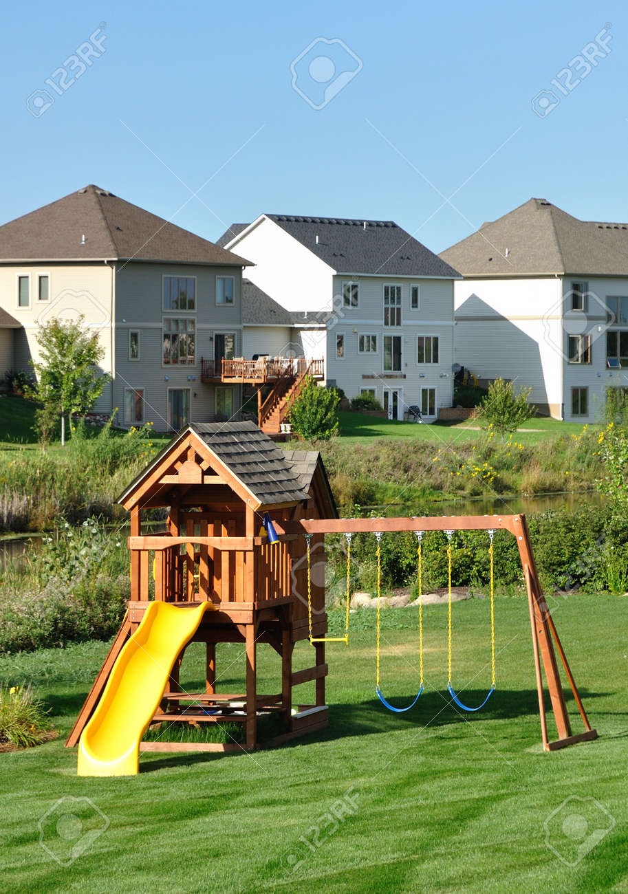 back yard wooden swing set on green lawn vertical stock photo