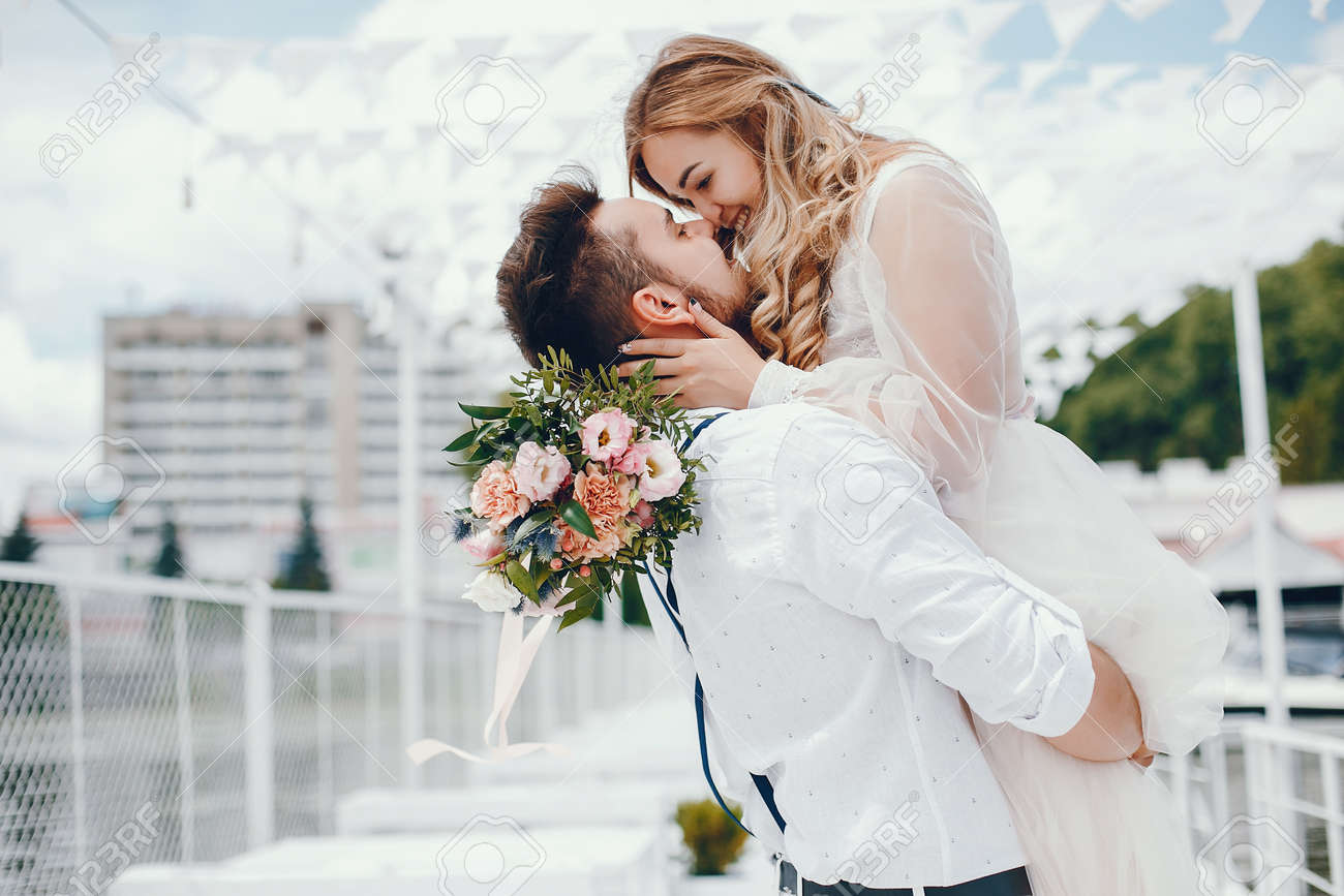 Beautiful bride with her husband in a park - 120382538