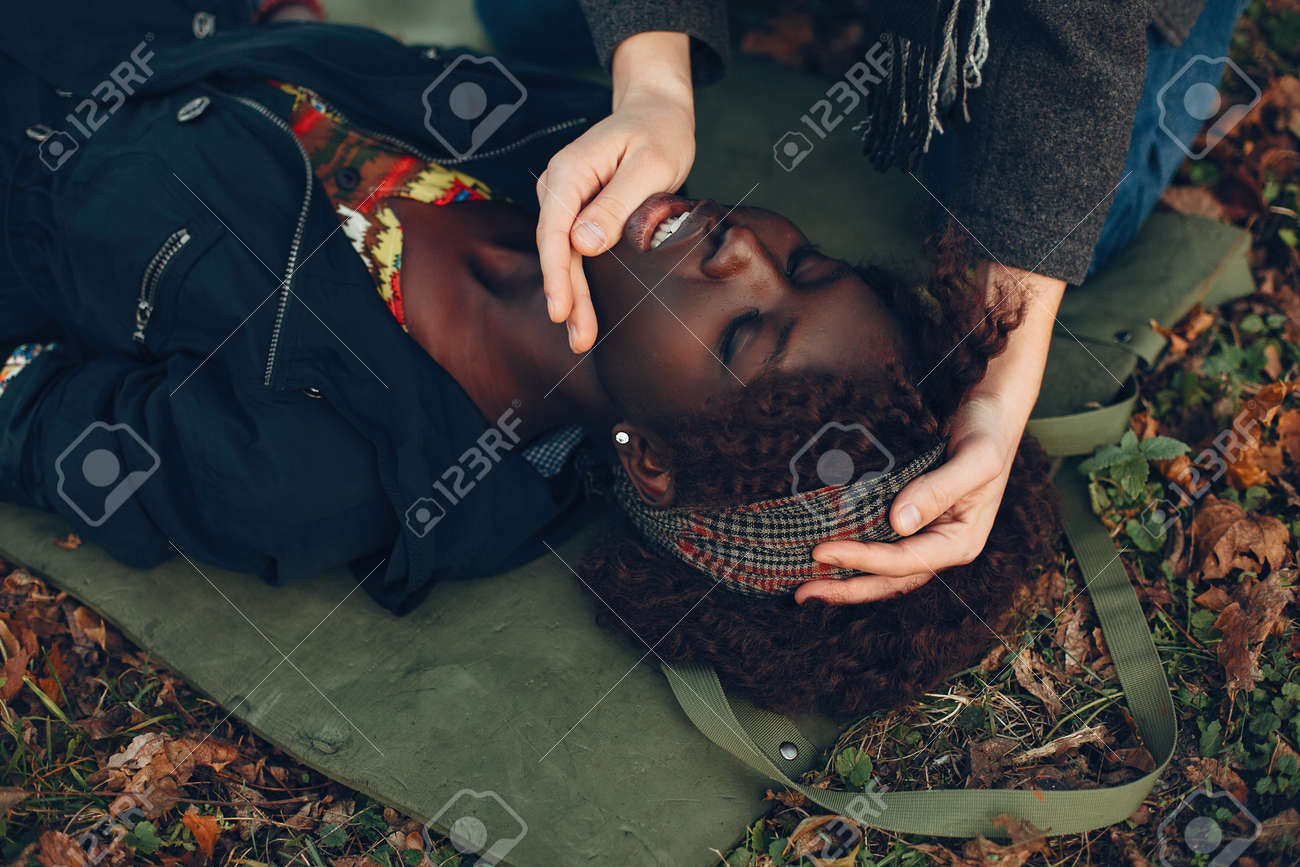 Man in a autumn park help a african girl - 156467127