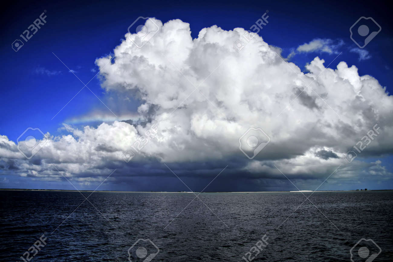 Big Cumulus Nimbus Cloud With Rainbow Sticking Out The Side. Stock ...
