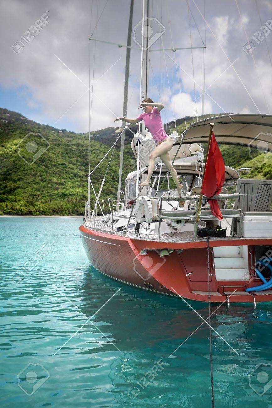 young woman jumping off the side of sailboat in the tropics stock