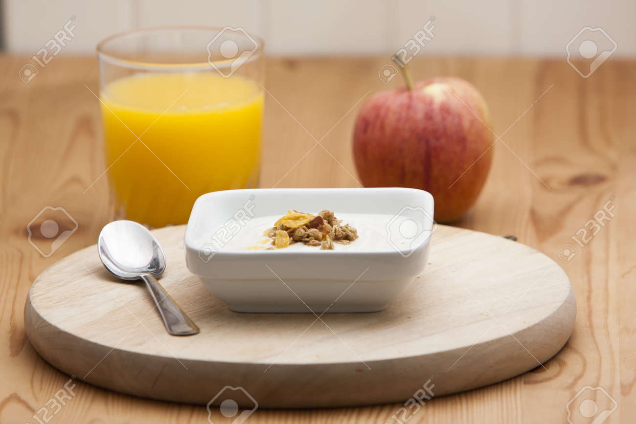Bowl of conflakes and yogurt on a wooden table with a spoon and a glass of orange juice and an apple Stock Photo - 9857608