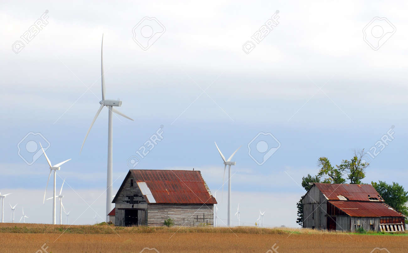 Old farm buildings surrounded by a modern wind farm Stock Photo - 8040499