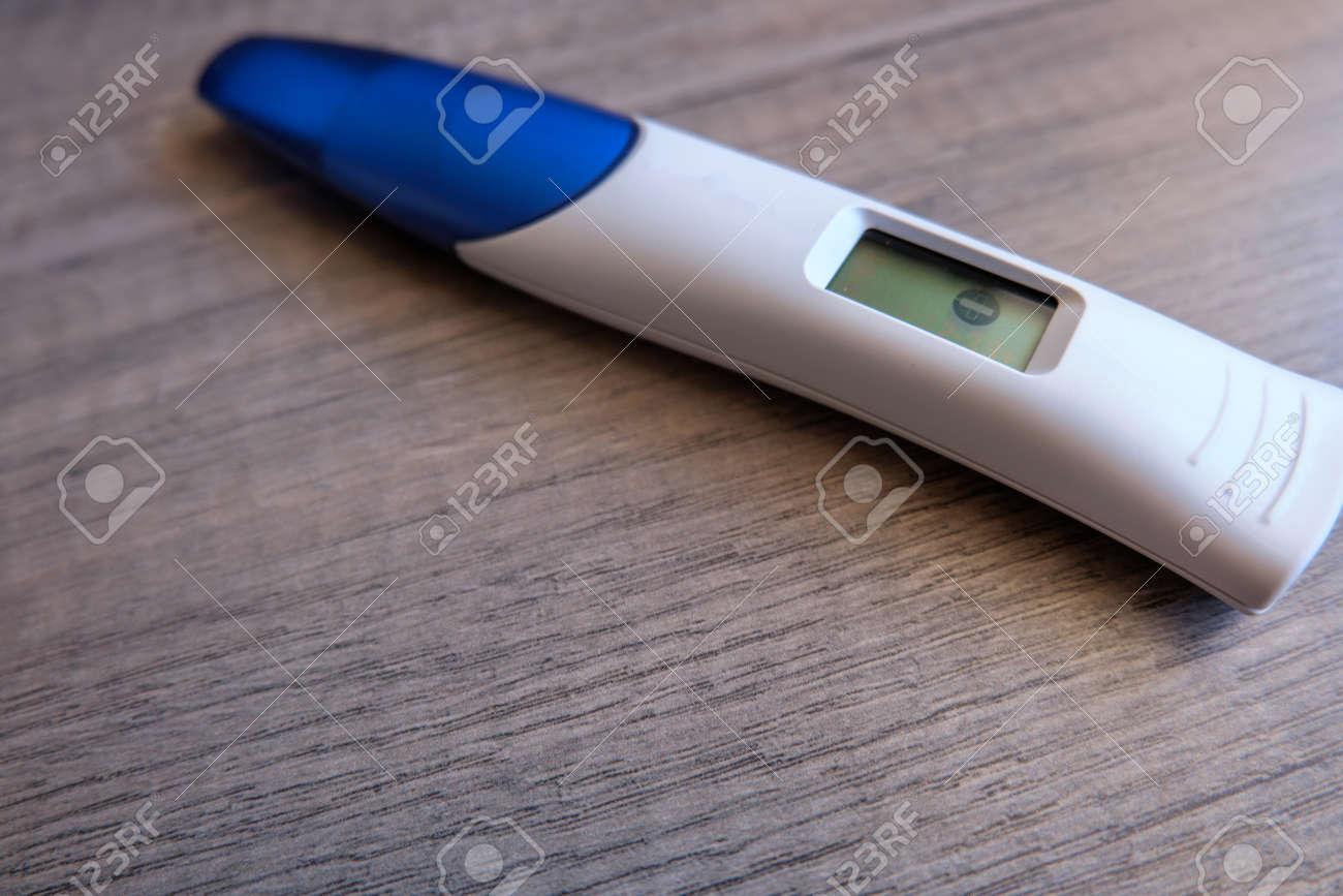 Digital pregnancy test with negative result on wooden background