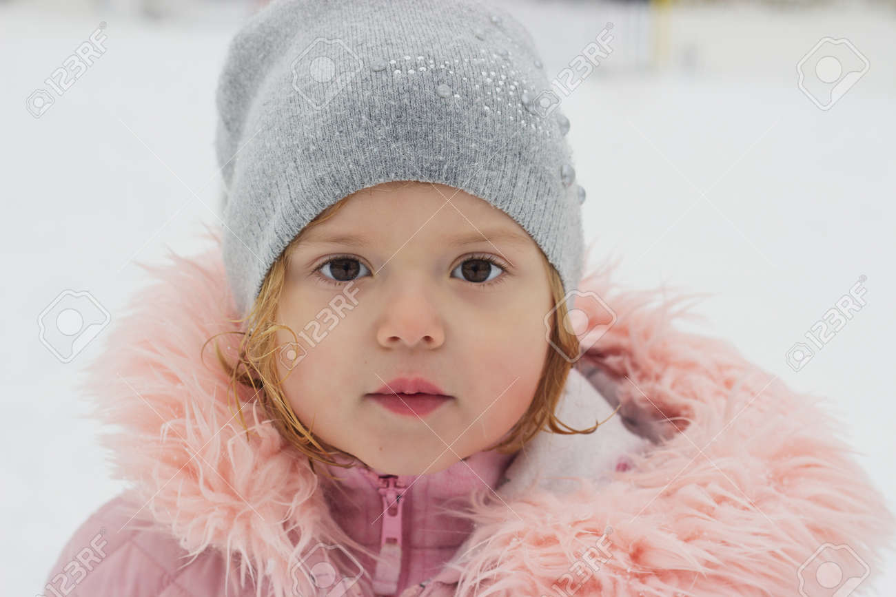 Beautiful little girl, looking at camera, winter portrait - 155900141