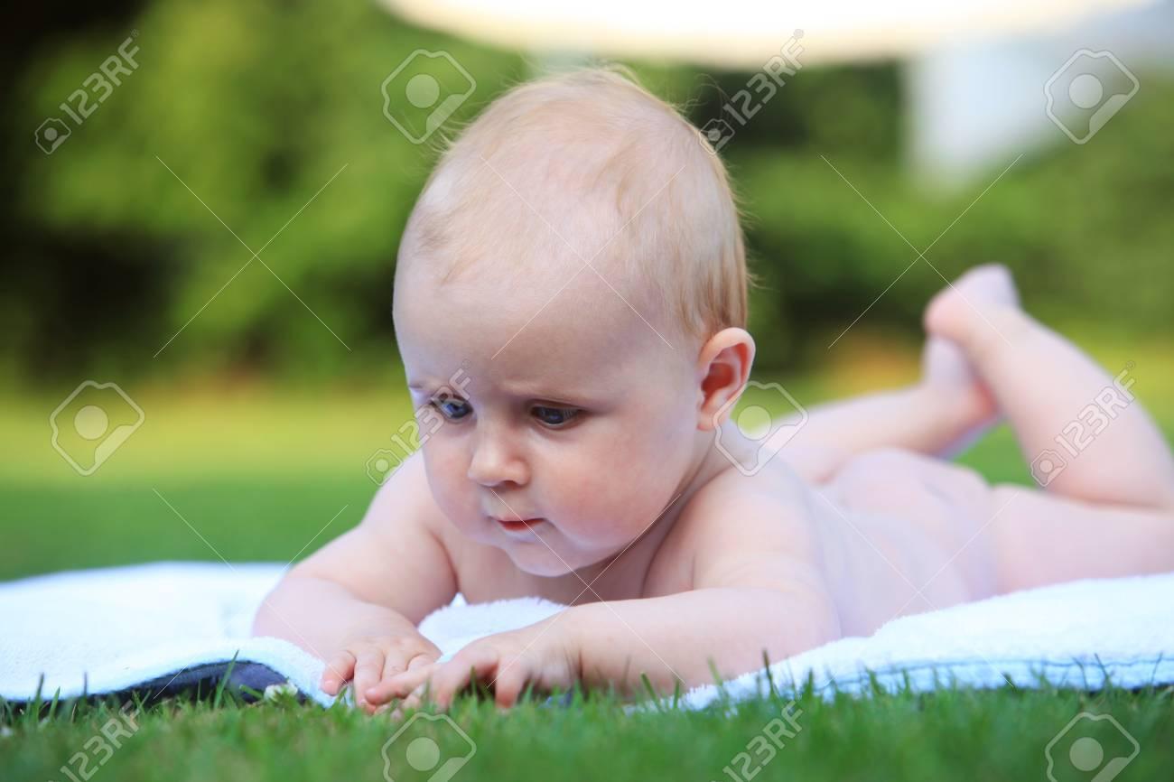 Cute baby su un asciugamano bianco è bagni di sole e giocare. baby è