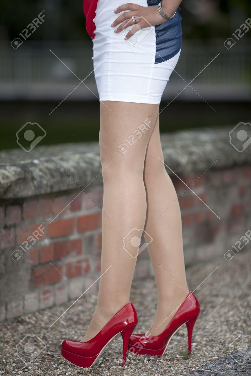 211d7b0e2 Red zapatos de tacón alto - Mujer con mini falda de pie con sus piernas  largas y medias blancas