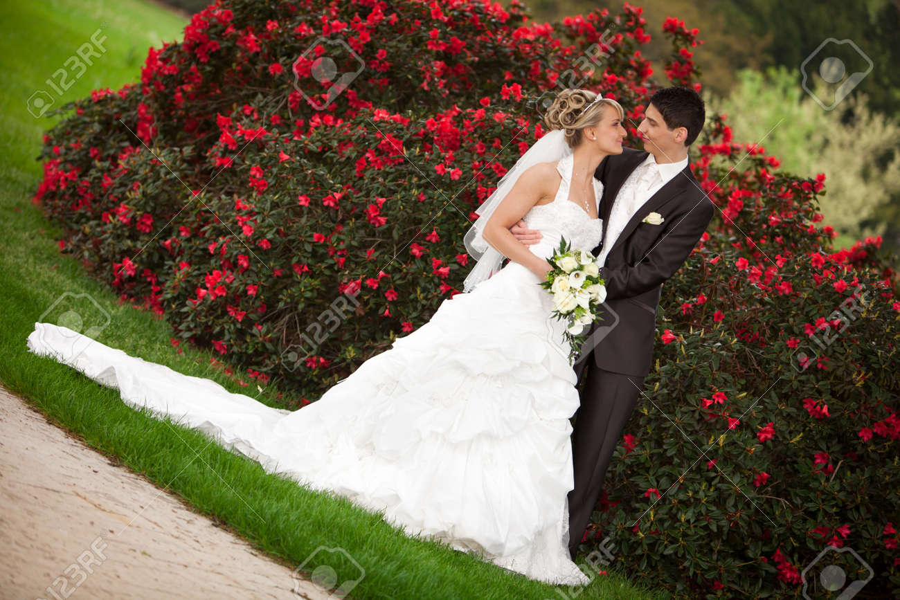 Young couple just married groom wants to kiss his pretty bride after the wedding ceremony she is blond and wearing a nice diadem background red roses and foreground yellow bouquet roses - 14018595