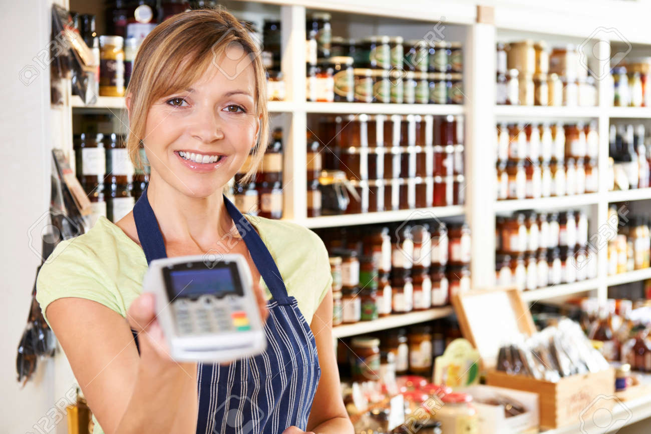 sales assistant in food store with credit card machine stock photo    stock photo   sales assistant in food store with credit card machine