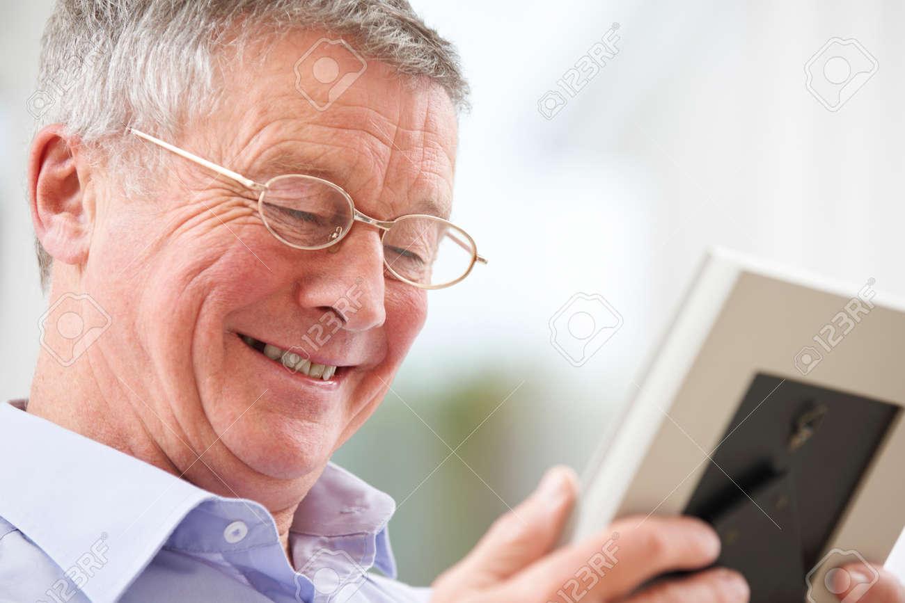 Sonriendo Hombre Mayor Que Mira La Fotografía En Marco Fotos ...